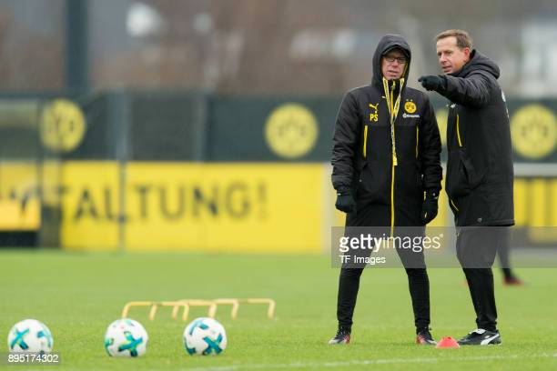 Head coach Peter Stoeger of Dortmund speaks with Assistant coach Joerg Heinrich of Dortmund during a training session at BVB trainings center on...