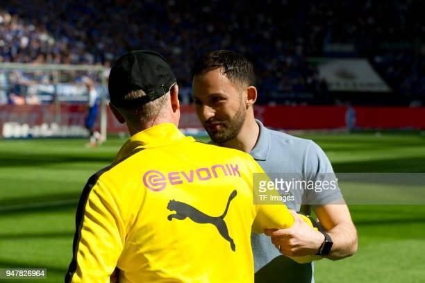 Head coach Peter Stoeger of Dortmund speaks with Head coach Domenico Tedesco of Schalke prior to the Bundesliga match between FC Schalke 04 and...