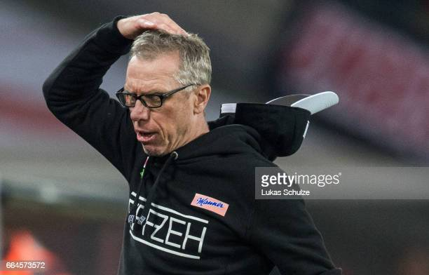 Head Coach Peter Stoeger of Koeln lost his cap during the Bundesliga match between 1 FC Koeln and Eintracht Frankfurt at RheinEnergieStadion on April...