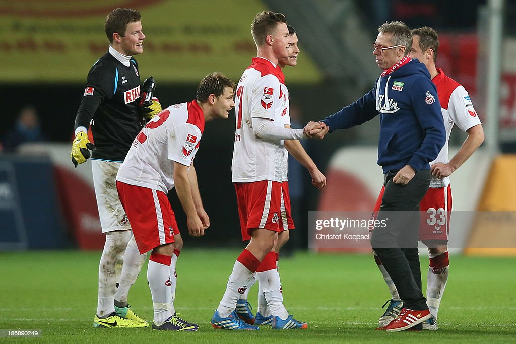 Head coach Peter Stoeger of Koeln (2nd R) shake hands with Yannick Gerhardt (3rd L) after the Second Bundesliga match between 1. FC Koeln and 1. FC Union Berlin at RheinEnergieStadion on November 4, 2013 in Cologne, Germany. The match between Koeln and Union Berlin ended 4-0.