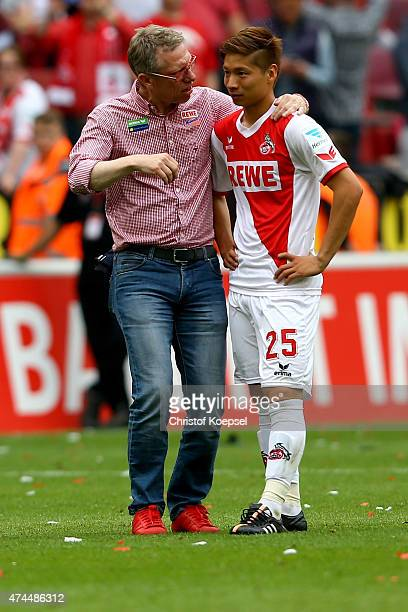 Head coach Peter Stoeger talks to Kazuki Nagasawa of Koeln after the Bundesliga match between 1 FC Koelan and VfL Wolfsburg at RheinEnergieStadion on...