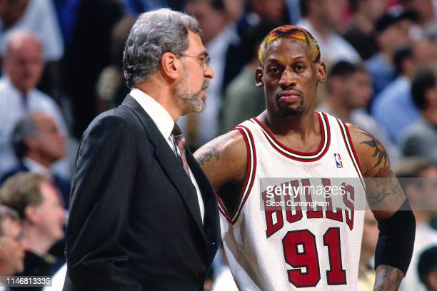 Head Coach Phil Jackson and Dennis Rodman of the Chicago Bulls talk during a game against the Charlotte Hornets during Game Five of the Eastern...