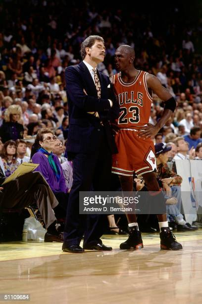 Head Coach Phil Jackson of the Chicago Bulls listens to a few words from Michael Jordan of the Chicago Bulls during a break in a game circa 1990....