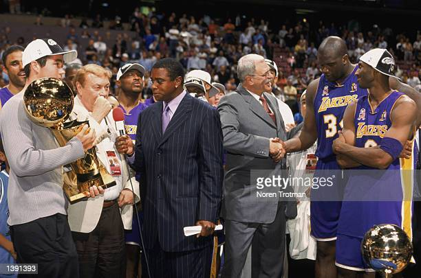 Head coach Phil Jackson of the Los Angeles Lakers congratulates guard Kobe Bryant and center Shaquille O'Neal as broadcaster Ahmad Rashaad of NBC...