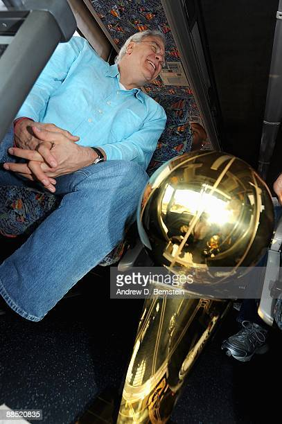 Head coach Phil Jackson of the Los Angeles Lakers smiles on the way to the airport as the Larry O'Brien trophy sits on the ground next to him on June...