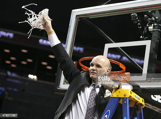 Head coach Phil Martelli of the Saint Joseph's Hawks holds up the net after cutting it down after defeating the Virginia Commonwealth Rams during the...