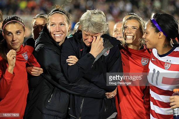 Head coach Pia Sundhage for the USA is surrounded by her players during a post game tribute after she coached her final game for the USA as they...