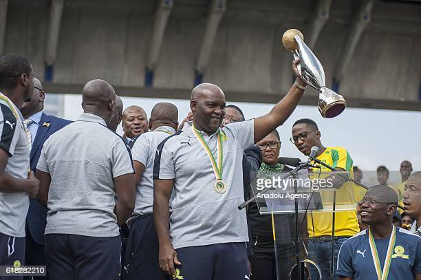 Head coach Pitso Mosimane of Mamelodi Sundowns holds the trophy as the team arrives at the Tambo Airport after they were crowned 2016 CAF Champions...