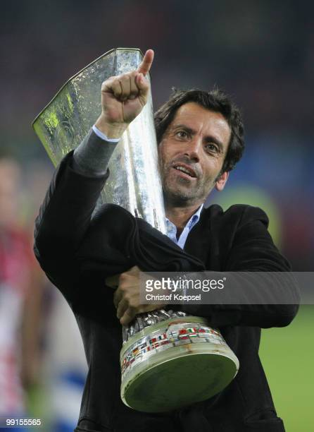 Head coach Quique Sanchez Flores of Atletico Madrid holds the UEFA Europa League trophy following his team's victory after extra time at the end of...