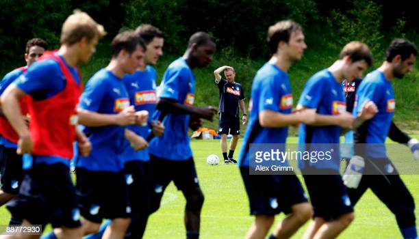 Head coach Ralf Rangnick watches his players jog during a training session of 1899 Hoffenheim during a training camp on July 1 2009 in Stahlhofen am...