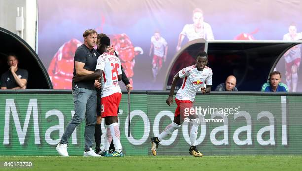 Head coach Ralph Hasenhuettl of Leipzig hugs Jean Kevin Augustin after his substitution next to Bruma of Leipzig during the Bundesliga match between...