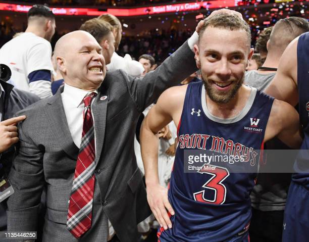 Head coach Randy Bennett of the Saint Mary's Gaels jokes with Jordan Ford as they celebrate their 6047 victory over the Gonzaga Bulldogs to win the...