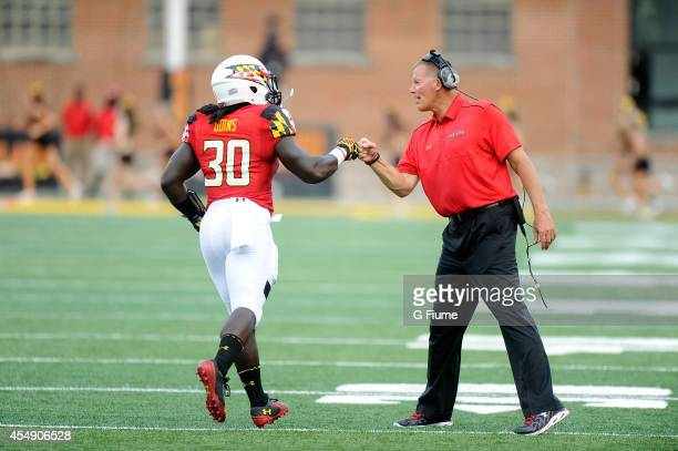 Head coach Randy Edsall of the Maryland Terrapins celebrates with Kenneth Goins Jr #30 after a touchdown against the James Madison Dukes at Byrd...
