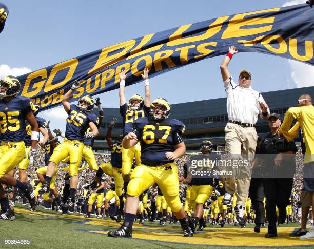 Head coach Rich Rodriguez enters the stadium with his team prior to playing the Western Michigan Broncos on September 5, 2009 at Michigan Stadium in...
