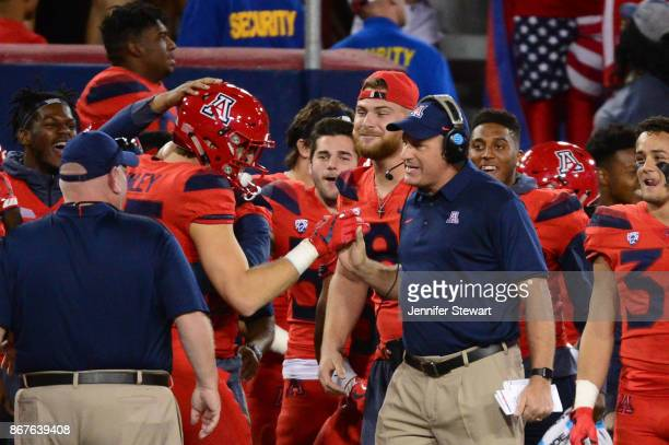 Head coach Rich Rodriguez of the Arizona Wildcats congratulates tight end Jamie Nunley after scoring a touchdown against the Washington State Cougars...
