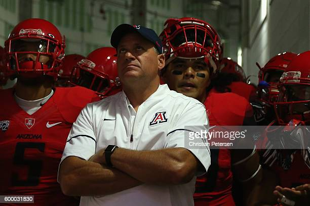 Head coach Rich Rodriguez of the Arizona Wildcats leads his team onto the field before the college football game against the Brigham Young Cougars at...
