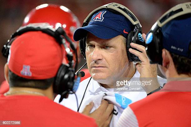 Head coach Rich Rodriguez of the Arizona Wildcats listens to other coaches in the game against Grambling State Tigers at Arizona Stadium on September...
