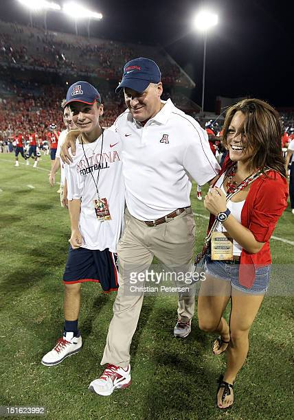 Head coach Rich Rodriguez of the Arizona Wildcats walks off the field with his son, Rhett, and daughter, Raquel, after defeating the Oklahoma State...