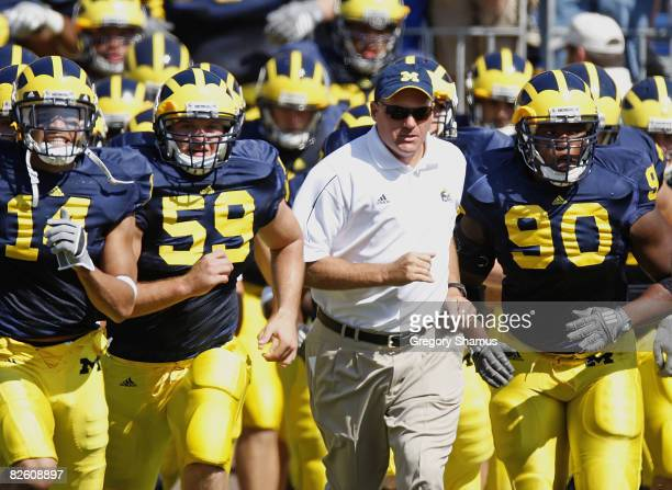 Head coach Rich Rodriguez of the Michigan Wolverines leads his team onto the field between Tim Jamison and Sean Griffin prior to playing the Utah...