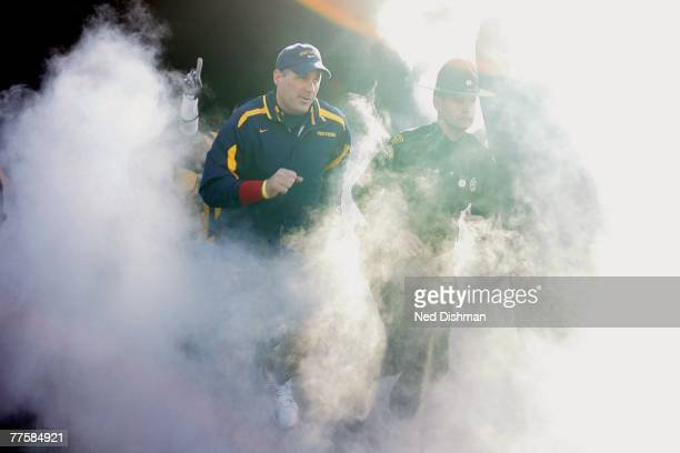 Head coach Rich Rodriguez of the West Virginia University Mountaineers runs out of the tunnel against the Mississippi State Bulldogs on October 20...