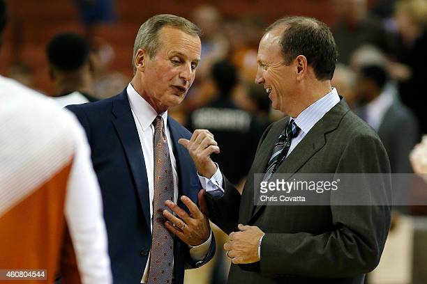Head coach Rick Barnes of the Texas Longhorns left talks with head coach Dan Monson of the Long Beach State 49ers before their teams play a game at...