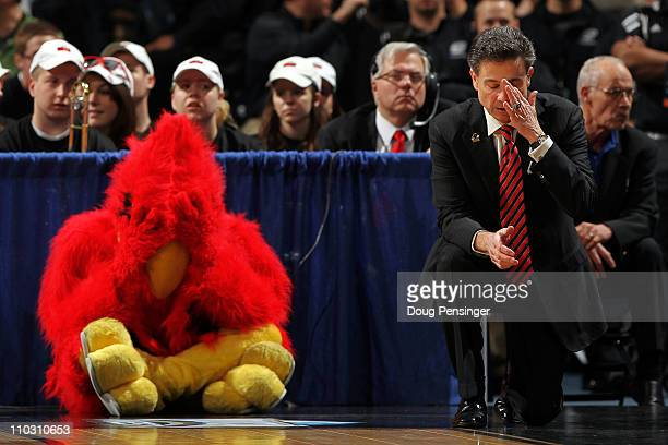 Head coach Rick Pitino of the Louisville Cardinals and the teams mascot react after a play while playing against the Morehead State Eagles during the...