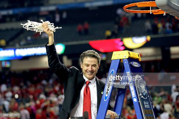 Head coach Rick Pitino of the Louisville Cardinals celebrates with the net after they won 82-76 against the Michigan Wolverines during the 2013 NCAA...