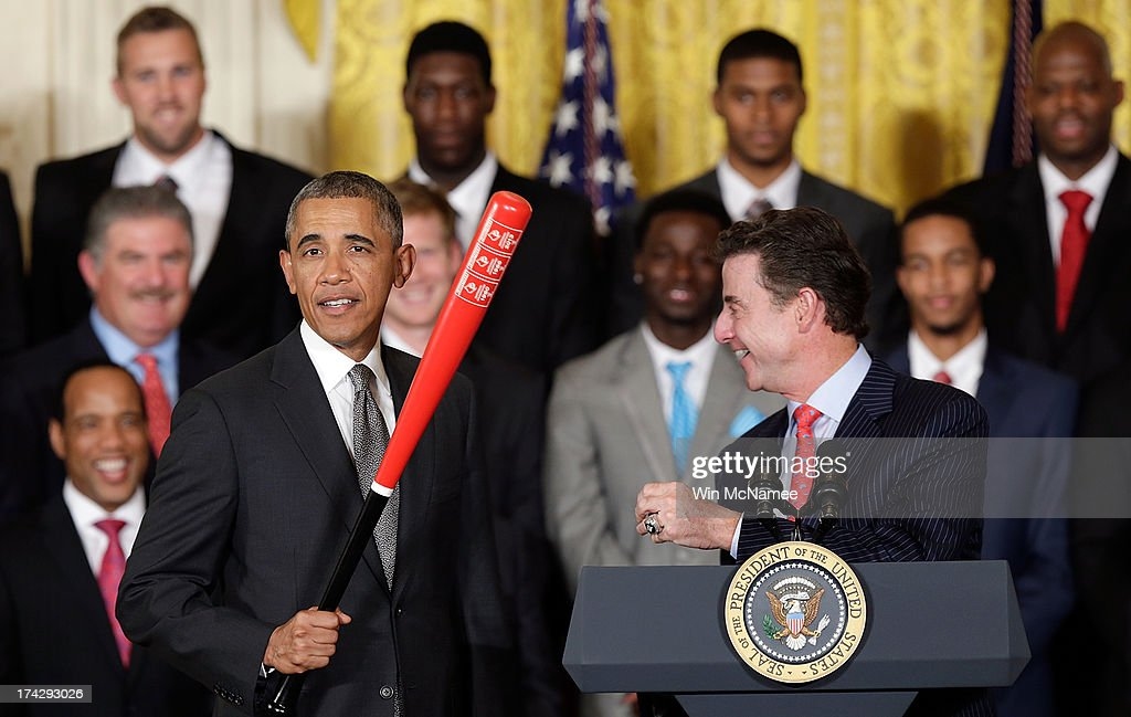 Head coach Rick Pitino (R) presents U.S. President Barack Obama with a Louisville Slugger baseball bat from the Louisville Cardinals, the 2013 NCAA Men's Basketball Champions, during an event in the East Room of the White House July 23, 2013 in Washington, DC. The Louisville Cardinals defeated the Michigan Wolverines in the championship game by a score of 82-76.