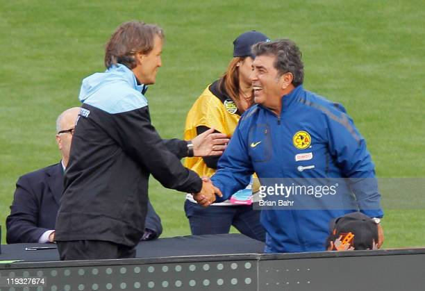 Head coach Roberto Mancini of Manchester City shakes hands with director tecnico Carlos Reinoso of Club America after their friendly match at ATT...