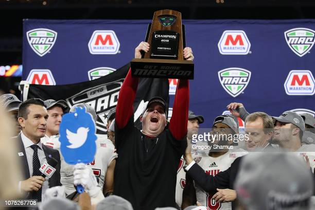 Head coach Rod Carey of the Northern Illinois Huskies celebrates with the MAC Championship trophy after defeating the Buffalo Bulls 3029 at Ford...