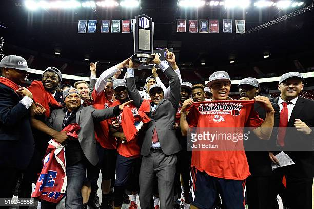 Head coach Rodney Terry of the Fresno State Bulldogs celebrates with players by hoisting the Mountain West Conference championship trophy with...