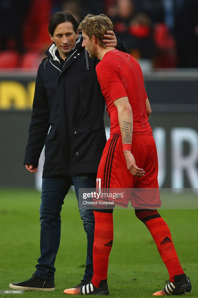 Head coach Roger Schmidt embraces Stefan Kiessling of Leverkusen after the Bundesliga match between Bayer 04 Leverkusen and SC Freiburg at BayArena on February 28, 2015 in Leverkusen, Germany. The match between Leverkusen and Freiburg ended 1-0.