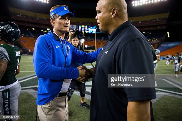 Head coach Ron Caragher of the San Jose State Spartans shakes hands with interim head coach Chris Naeole of the Hawaii Warriors after a college...