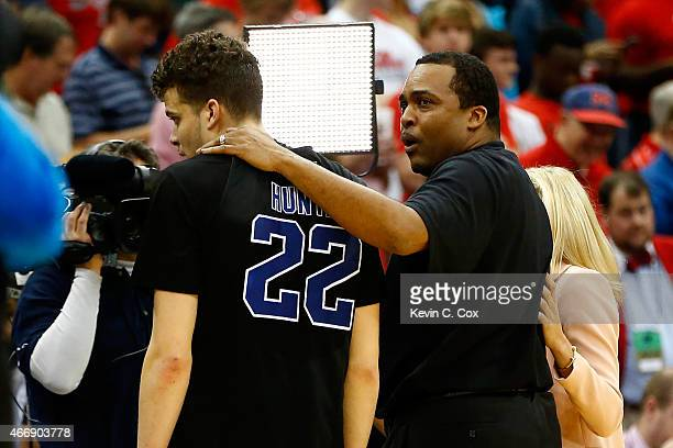 Head coach Ron Hunter of the Georgia State Panthers puts his arm around son and player R.J. Hunter after the Panthers 57-56 win against the Baylor...
