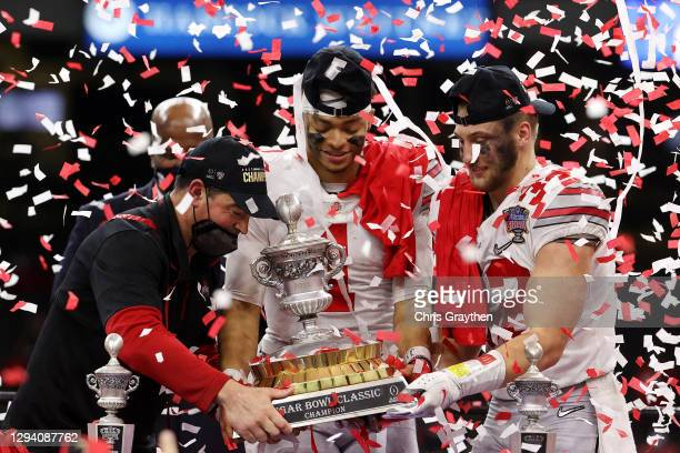 Head coach Ryan Day, Justin Fields and Tuf Borland of the Ohio State Buckeyes lift the trophy after defeating the Clemson Tigers 49-28 during the...