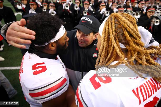 Head coach Ryan Day of the Ohio State Buckeyes celebrates a 5727 win over the Michigan Wolverines with Chase Young and Baron Browning at Michigan...