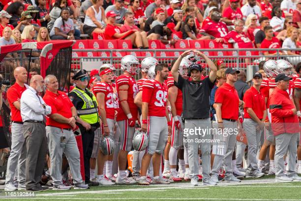 Head coach Ryan Day of the Ohio State Buckeyes forms an IO towards Ohio State Buckeyes fans in the stands during game action between the Ohio State...