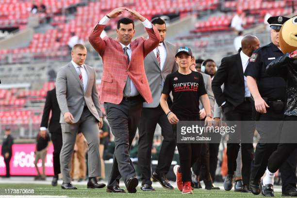 """Head Coach Ryan Day of the Ohio State Buckeyes salutes fans with an """"O"""" as he walks through Ohio Stadium before a game against the Michigan State..."""