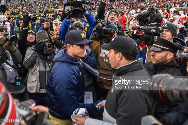 Head Coach Ryan Day of the Ohio State Buckeyes shakes hands with Head Coach Jim Harbaugh of the Michigan Wolverines after a college football game at...