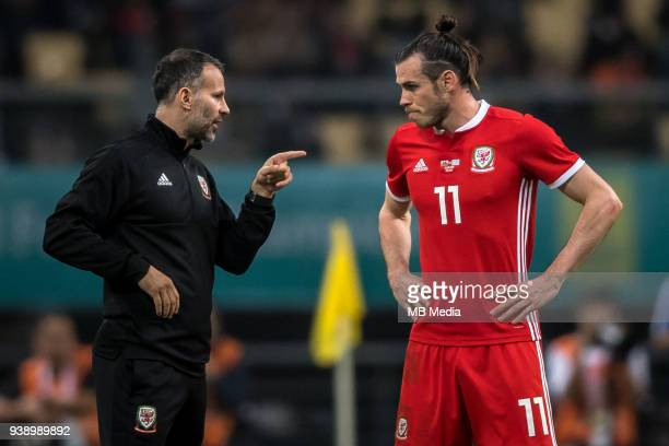 Head coach Ryan Giggs left of Wales national football team instrucs his player Gareth Bale as they compete against Uruguay national football team in...