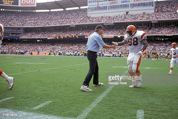 Head coach Sam Wyche of the Cincinnati Bengals greets David Grant as he walks to the sidelines during a game against the Los Angeles Rams at the...