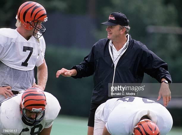 Head Coach Sam Wyche of the Cincinnati Bengals talks to Boomer Esiason of the Cincinnati Bengals during practice on August 23 1989 in Cincinnati Ohio