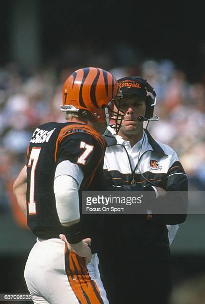 Head coach Sam Wyche of the Cincinnati Bengals talks with his quarterback Boomer Esiason during an NFL football game circa 1989 at Riverfront Stadium...