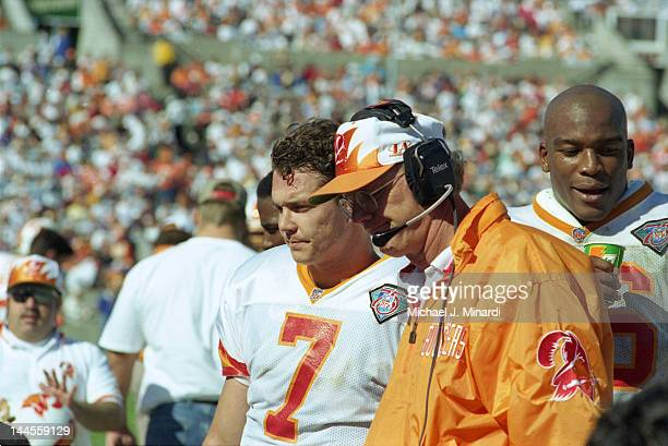 Head Coach Sam Wyche of the Tampa Bay Buccaneers goes over a set of plays before the game with the Quarterback Craig Erickson and some other players...