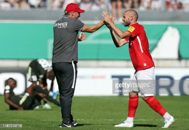 Head coach Sascha Hildmann of Kaiserslautern celebrates with Manfred Starke after the DFB Cup first round match between 1 FC Kaiserslautern and 1 FSV...