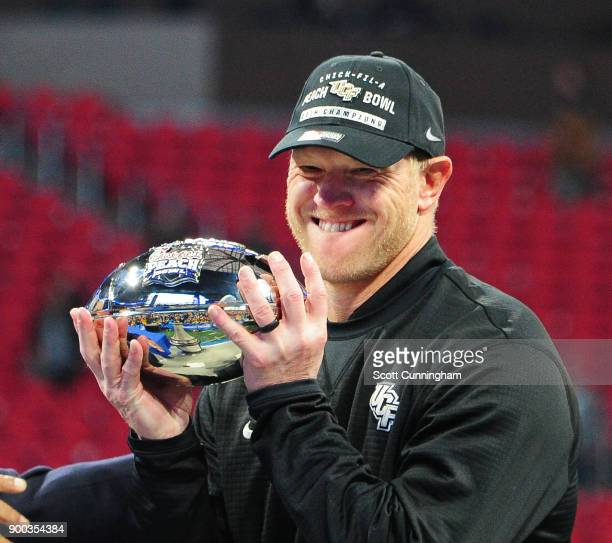 Head Coach Scott Frost of the Central Florida Knights accepts the championship trophy for winning the ChickfilA Peach Bowl against the Auburn Tigers...