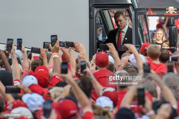Head coach Scott Frost of the Nebraska Cornhuskers exits the bus in front of fans before the game against the Akron Zips at Memorial Stadium on...