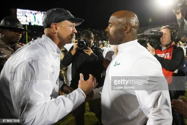 Head coach Scott Frost of the UCF Knights and head coach Charlie Strong of the South Florida Bulls shake hands after a game at Spectrum Stadium on...