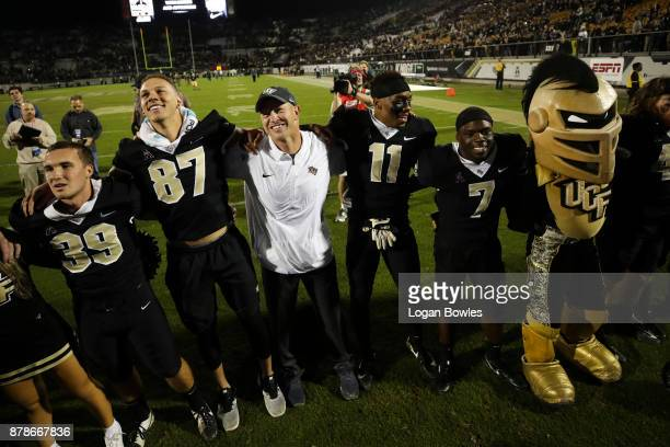 Head coach Scott Frost of the UCF Knights celebrates with his team after a game against the South Florida Bulls at Spectrum Stadium on November 24...
