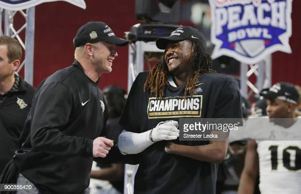 Head coach Scott Frost of the UCF Knights celebrates with Shaquem Griffin after defeating the Auburn Tigers 3427 to win the ChickfilA Peach Bowl at...